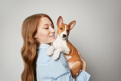 Beautiful red haired girl embracing puppy on white background. Studio portrait of white appealing woman chilling with. Dog royalty free stock photo