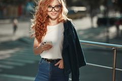 Beautiful red-haired girl with a beautiful figure and a phone in her hands. The girl communicates on her modern gadget with her. Relatives and friends. She is royalty free stock photo
