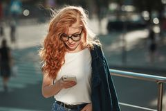 Beautiful red-haired girl with a beautiful figure and a phone in her hands. The girl communicates on her modern gadget with her. Relatives and friends. She is stock image