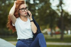 Beautiful red-haired girl with a beautiful figure and a phone in her hands. The girl communicates on her modern gadget with her. Relatives and friends. She is royalty free stock photography