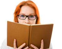 Beautiful red-haired girl in glasses with book. Stock Images