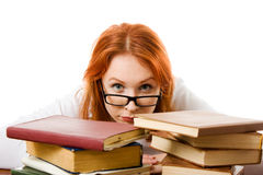 Beautiful red-haired girl in glasses with books. Royalty Free Stock Images