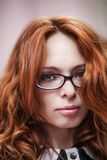 Beautiful red-haired girl in glasses. Royalty Free Stock Image