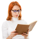 Beautiful red-haired girl in glasses reads book. Stock Photos