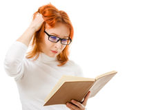 Beautiful red-haired girl in glasses reads book. Royalty Free Stock Photo