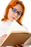 Beautiful red-haired girl in glasses reads book. Royalty Free Stock Images