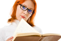 Beautiful red-haired girl in glasses reads book. Stock Photo