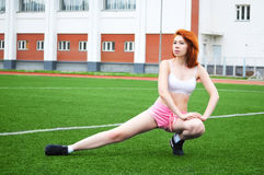 Beautiful red-haired girl goes in for sports and doing workout at the stadium. On the green grass Royalty Free Stock Photography