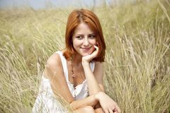 Beautiful red-haired girl at grass Stock Photography
