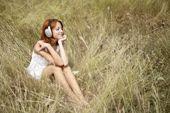 Beautiful red-haired girl at grass with headphones Royalty Free Stock Photo