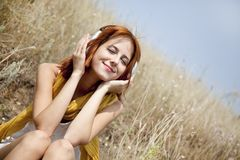 Beautiful red-haired girl at grass with headphones Stock Images