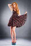 Beautiful red-haired girl on grey background Stock Image