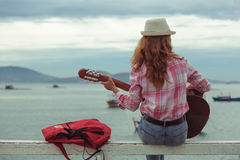 Beautiful red-haired girl with a guitar. Beautiful red-haired girl sitting on a fence with a guitar on the beach royalty free stock photos
