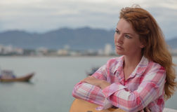 Beautiful red-haired girl with a guitar. Beautiful red-haired girl sitting on a fence with a guitar on the beach stock photo