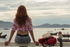 Beautiful red-haired girl with a guitar. Beautiful red-haired girl sitting on a fence with a guitar on the beach stock photos