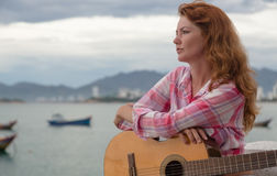 Beautiful red-haired girl with a guitar. Beautiful red-haired girl sitting on a fence with a guitar on the beach royalty free stock photography