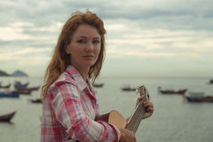 Beautiful red-haired girl with a guitar Royalty Free Stock Image
