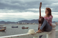 Beautiful red-haired girl with a guitar. Beautiful red-haired girl sitting on a fence with a guitar on the beach royalty free stock photo