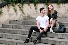 Beautiful red haired girl and guy brunette cute chat sitting on the stairs royalty free stock photo