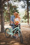 Beautiful red-haired girl with a guy standing in a forest holding flowers in hands. royalty free stock photography