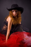 Beautiful red-haired girl in hat. Over gray background stock image
