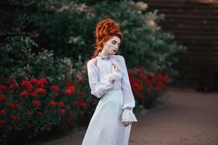 Beautiful red-haired girl with a high hair in an old white dress Royalty Free Stock Image