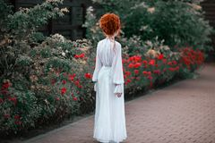Beautiful red-haired girl with a high hair in an old white dress. In the park. The Victorian era. Historic costume. White Queen. Princess castle royalty free stock images