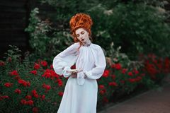 Beautiful attractive girl with red hair. Beautiful red-haired girl with a high hair in an old white dress in the park. The Victorian era. Historic costume. White stock images
