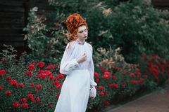 Beautiful red-haired girl with a high hair in an old white dress Stock Photo