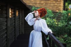 Beautiful red-haired girl with a high hair in an old white dress stock images