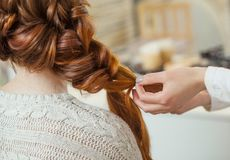 Beautiful, red-haired girl with long hair, hairdresser weaves a French braid. In a beauty salon. Professional hair care and creating hairstyles stock photos