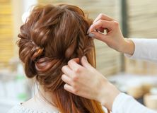 Beautiful, red-haired girl with long hair, hairdresser weaves a French braid, in a beauty salo. N. Professional hair care and creating hairstyles royalty free stock photography