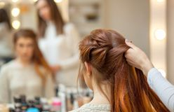 Beautiful, red-haired girl with long hair, hairdresser weaves a French braid, in a beauty salon. Professional hair care and creating hairstyles stock photo