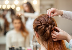 Beautiful, red-haired girl with long hair, hairdresser weaves a French braid, in a beauty salon. Professional hair care and creating hairstyles stock photography
