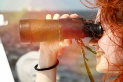 Beautiful red-haired girl looking through binoculars. Marine walk. Spotting on a boat trip.Observation Royalty Free Stock Photos