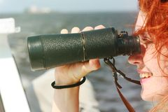 Beautiful red-haired girl looking through binoculars. Marine walk. Observation Stock Photo
