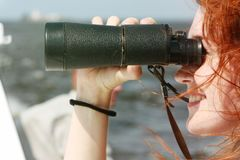 Beautiful red-haired girl looking through binoculars. Marine walk. Observation Royalty Free Stock Photo