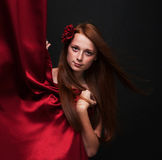 Beautiful red-haired girl looks out from behind a red theater cu Royalty Free Stock Image