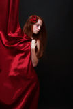 Beautiful red-haired girl looks out from behind a red theater cu Royalty Free Stock Photos