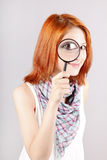 Beautiful red-haired girl with loupe. Zooming her eye Royalty Free Stock Photos