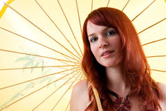 Beautiful red haired girl with parasol. Beautiful red-headed girl with yellow parasol stock photos