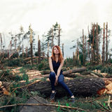 Beautiful red-haired girl in pine forest. Sitting stock image