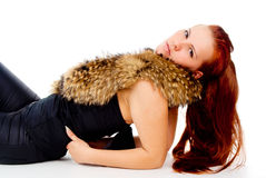 A beautiful red-haired girl posing with fur Stock Image