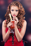 Beautiful red-haired girl in a red cocktail dress Stock Photos