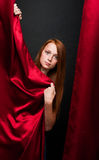Beautiful red-haired girl with red curtains on a dark background Stock Photography