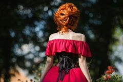 Beautiful red-haired girl in a red dress and in black corset on a green background. Royalty Free Stock Photos