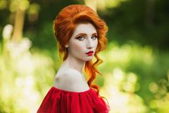 Beautiful red-haired girl in a red dress on a green background. Beautiful red-haired girl in red dress posing on green background. Portrait of a woman with red royalty free stock image