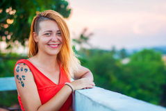 Beautiful red-haired girl in a red dress and tattooed laughs on the veranda of a summer restaurant Stock Photo