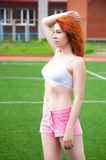 Beautiful red-haired girl resting after exercising in the stadium Royalty Free Stock Photography