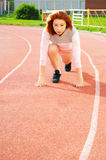 Beautiful red-haired girl running on the stadium Royalty Free Stock Image